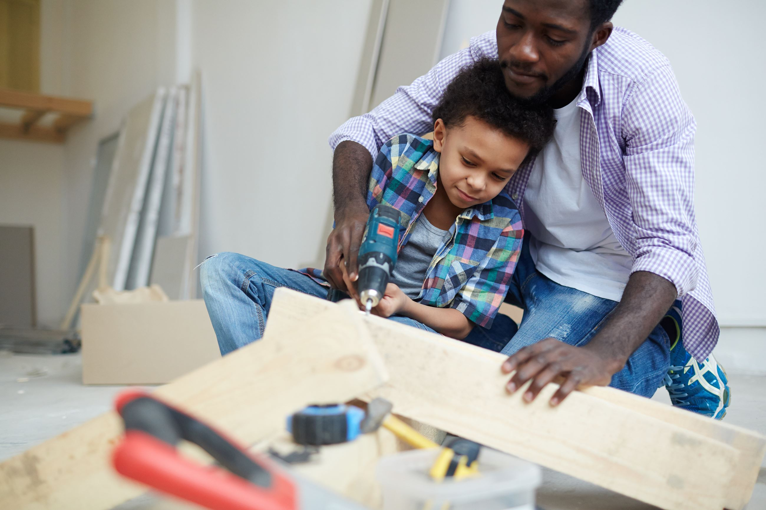 storyblocks-young-man-showing-his-son-how-to-work-with-electric-drill_HUXpoN8w0b